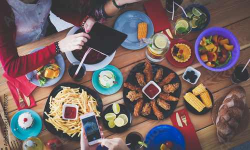 Photo Stands Grill / Barbecue Top view of group of people having dinner together while sitting at wooden table. Food on the table. People eat fast food.