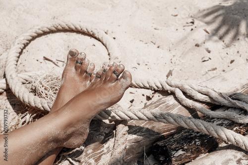 Poster Tunesië close up of beautiful woman legs on wild beach
