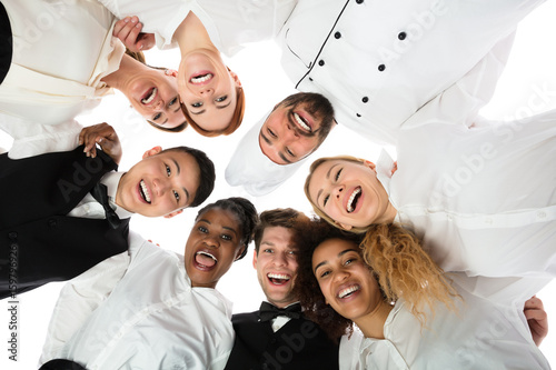 Fotomural Smiling Restaurant Staff Standing Against White Background