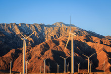 Sunrise Creates A Beautiful Winter Contrast Between The Wind Turbines And Mountains.