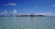 v03934 Aerial flying drone view of Maldives white sandy beach 2 people young couple man woman romantic love on sunny tropical paradise island with aqua blue sky sea water ocean 4k