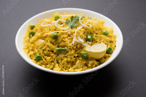 Deurstickers Klaar gerecht Indian Breakfast Dish Poha Also Know as Pohe or Aalu poha made up of Beaten Rice or Flattened Rice. The rice flakes are lightly fried in oil with mustard, chilly, onion, curry leaves and turmeric