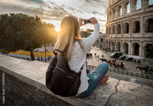 Woman tourist selfie with phone camera in hands near the Coliseu Canvas Print