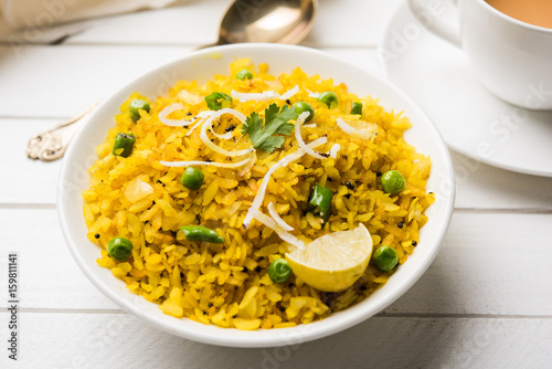 Poster Klaar gerecht Indian Breakfast Dish Poha Also Know as Pohe or Aalu poha made up of Beaten Rice or Flattened Rice. The rice flakes are lightly fried in oil with mustard, chilly, onion & turmeric, served with hot tea