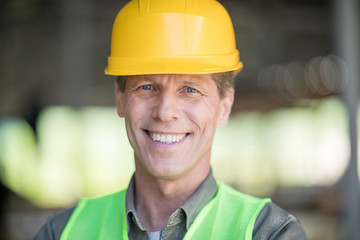 Close-up portrait of middle aged builder in hard hat smiling at camera