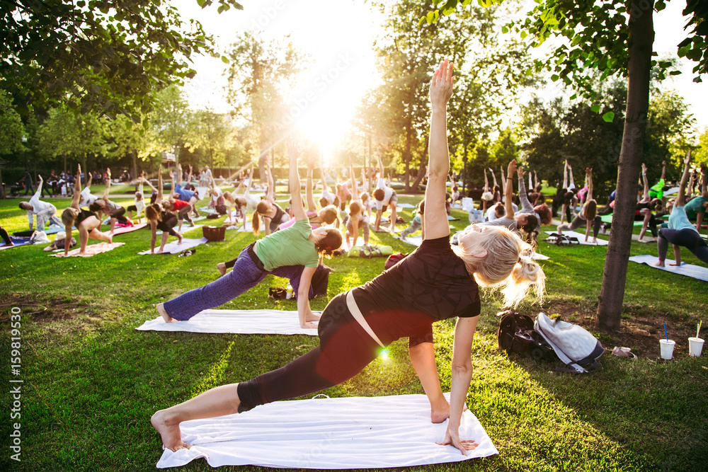 Fototapeta big group of adults attending a yoga class outside in park