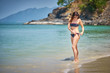 Young caucasian woman in black bikini standing on the shore of a tropical beach Pentai Tengah at Langkawi island, Malaysia
