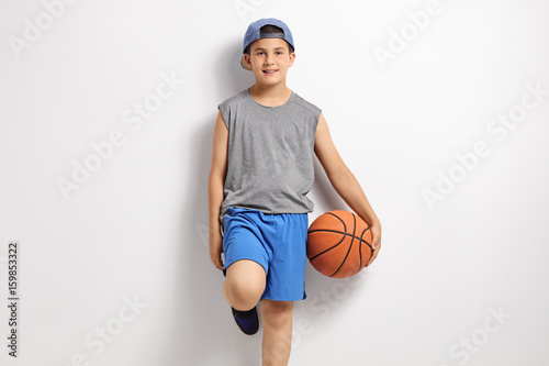 Boy with basketball leaning against a wall
