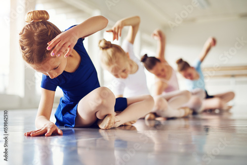 Poster Dance School Girls bending sitting on floor in ballet class