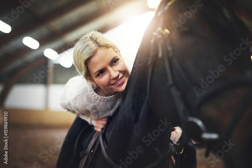 Cheerful blonde?female sitting?astride?black horse Fototapet