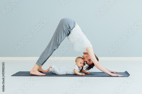 Staande foto School de yoga young mother does physical yoga exercises together with her baby boy