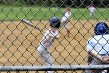 Soft Baseball Players Seen Through Backstop