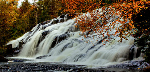Fototapeta Jesień Michigan Autumn Waterfall. Beautiful Bond Falls in northern Michigan surrounded by vibrant fall foliage. This natural landmark is located within a small state park scenic site in the Upper Peninsula.