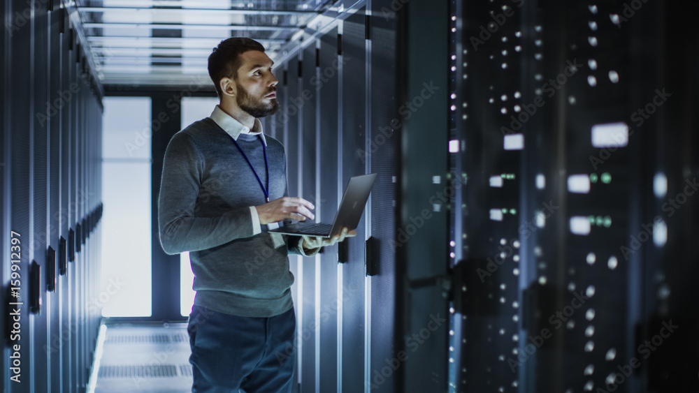 Fototapety, obrazy: IT Technician Works on Laptop next to a Server Cabinet in Big Data Center. He Runs Diagnostics and Maintenance, Sets System Up.