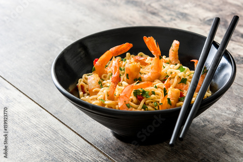 Noodles and shrimps with vegetables in black bowl on wooden table
