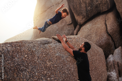Fototapety, obrazy: Little boy leaping into his father's arms at the beach