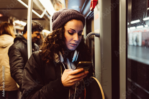 Young woman using smartphone while traveling in subway train