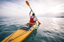 Rear View Of Man Paddling Sea Kayak