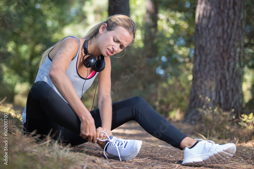 Photo female runner touching foot in pain due to sprained ankle