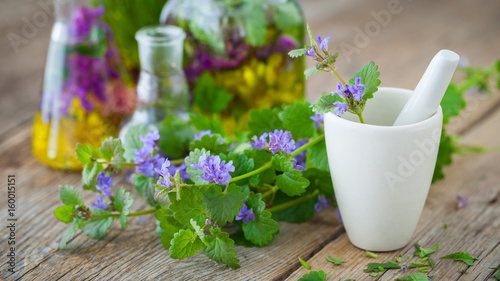 Photo  Mortar of healing herbs and bottles of healthy tincture or infusion on background