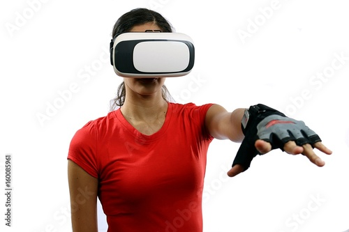 2d0805dcc436 Young attractive woman wearing virtual reality goggles and remote control  glove