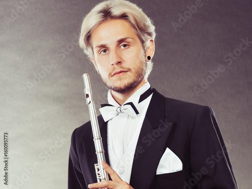 Plakat Elegancko ubrany muzyk trzyma flet