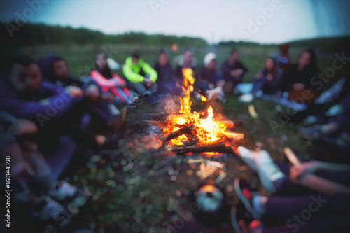 Obraz Friends are sitting around the bonfire - fototapety do salonu