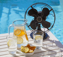 Hot Summer Day During A Heat Wave. A Jar Of Refreshing Water And A Vintage Fan At The Pool.