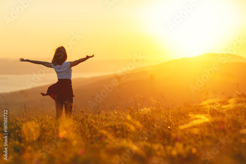 Foto Happy woman standing with her back on sunset in nature iwith open hands