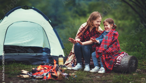 Poster Camping Family mother and child daughter warm their hands by bonfire on camping trip with tent