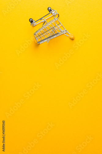 Fotografía  shopping trolley upside down on yellow background with some copy space