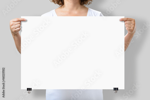 Fotografía  Woman holding a blank A2 poster mockup isolated on a gray background
