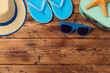 Summer vacation background with flip flops, sunglasses and hat on wooden board. View from above