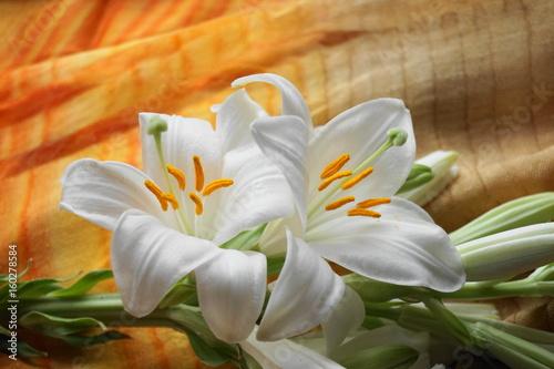biala-lilia-z-pomaranczowymi-elementami-na-tkaninie