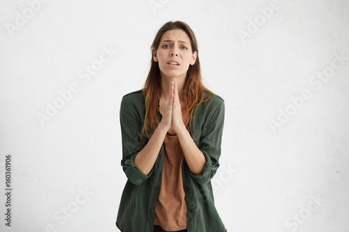 Fotografía  Worried apologetic brunette woman having some difficulties pressing her palms together begging for apologize