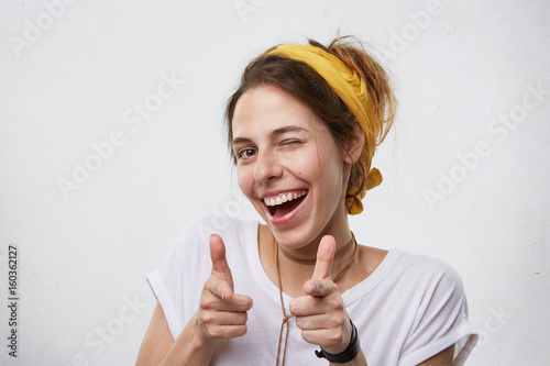 Positive cheerful young woman wearing yellow scarf on head and white casual T-shirt blinking her eyes and smiling pointing at camera with index fingers Wallpaper Mural