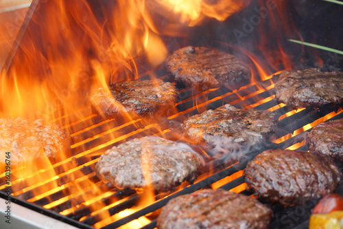 Staande foto Grill / Barbecue barbecue grill cooking burger steak on the fire