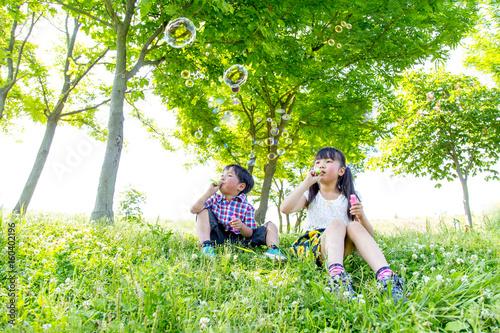 Fotografia  新緑の樹木の前でシャボン玉で遊ぶ姉弟の子供