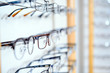 canvas print picture - in optician shop- different  glasses for sale in wall rack