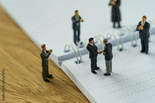 Fotografie, Obraz  Miniature people with small figure businessmen handshaking and others clapping o