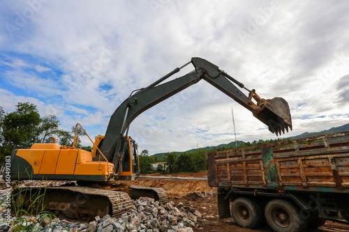 Fototapeta Ekskawator lub backhoe przy budową z niebieskim niebem i zmierzchem, ciężkim przemysłem i bezpieczeństwem przy pracy pojęciem ,.
