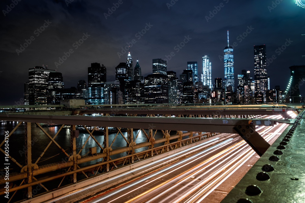 View from the Brooklyn Bridge at night with the One World Trade Center and traff Poster