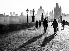 Foggy Morning On Charles Bridge, Prague, Czech Republic. Sunrise With Silhouettes Of Walking People, Statues And Old Town Towers. Romantic Travel Destionation. Black And White Image.