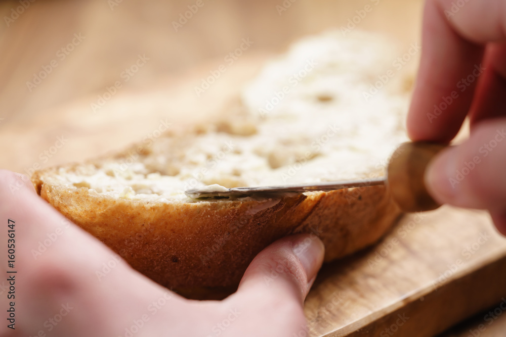 Fototapety, obrazy: young female hands spreading butter on bread