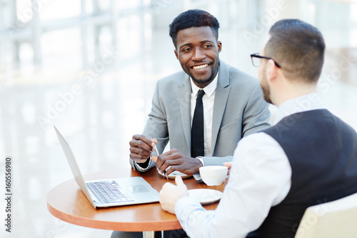 Obraz Portrait of successful African-American businessman smiling while discussing deal with partner during meeting at coffee break - fototapety do salonu