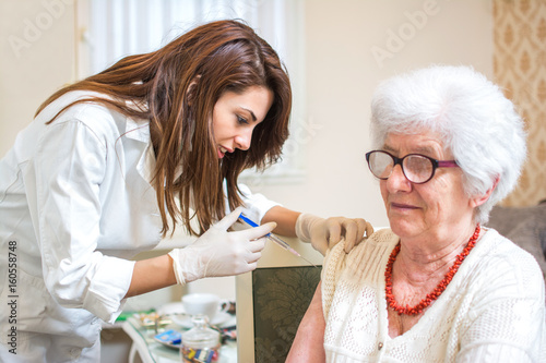 Home healthcare nurse giving injection to elderly woman. – kaufen ...