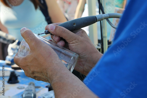 Fototapeta The work of the engraver on glass, engraving on a glass obraz