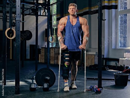Stampa su Tela Bodybuilder on crutches in a gym club.