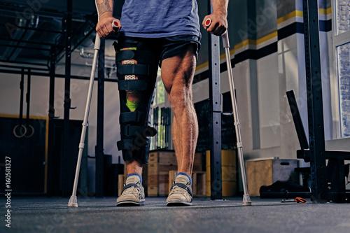 Fototapeta Injured bodybuilder's leg in bandage with crutches.