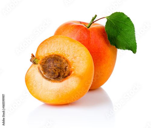 Ripe apricot fruits with with green leaf and slice isolated